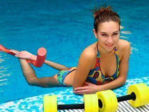 Гантели для занятий аквааэробикой и девушка на бассейне