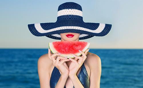 Девушка в шляпе держит кусочек арбуза