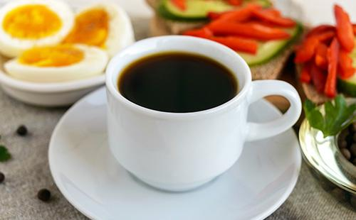 Чашка крепкого кофе, варёные яйца и овощи на завтрак