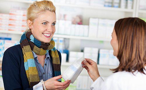 Довольная женщина с покупкой в аптеке