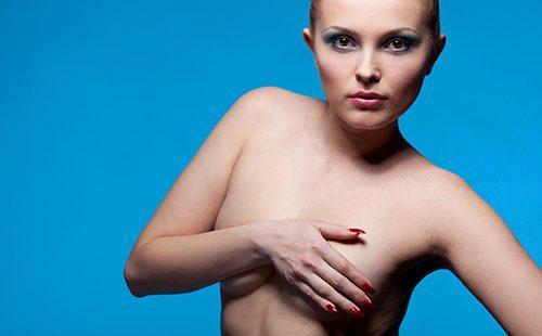 Обнажённая девушка прикрывает грудь
