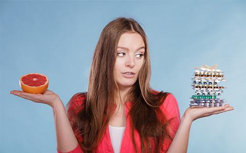 Девушка выбирает между таблетками и едой