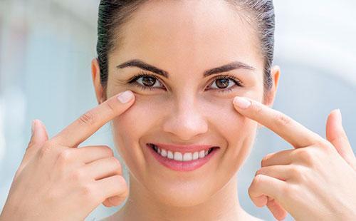 Девушка показывает на кожу под глазами