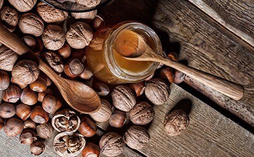 Банка мёда и разные орехи на деревянном столе