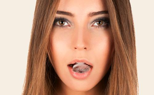 Девушка держит кубик льда во рту