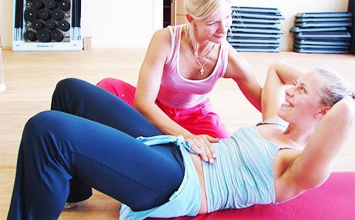 Женщина занимается спортом с инструктором