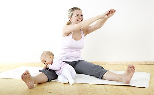 Женщина делает зарядку дома с малышом