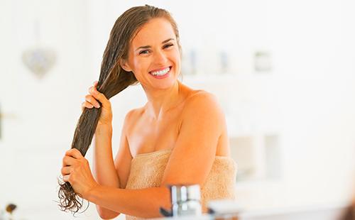 Счастливая женщина держит в руках мокрые волосы