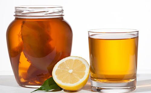 Чайный гриб в банке, лимон и кружка с чаем
