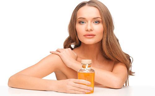 Молодая женщина держит бутылочку с маслом