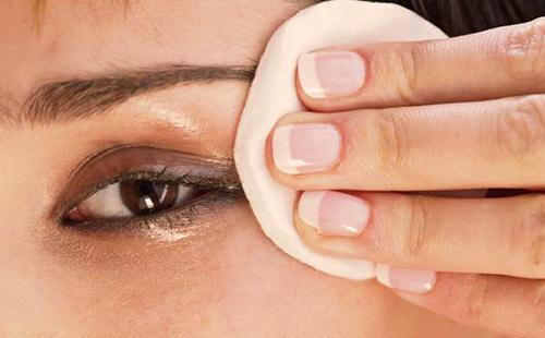 Кареглазая красавица вытирает глаз ватным диском