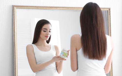 Девушка держит банку с кокосовым маслом
