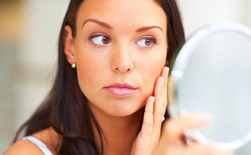 Кареглазая девушка строго рассматривает свои щёчки в зеркале