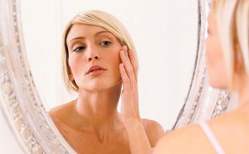 Блондинка внимательно рассматривает в зеркале кожу в уголках глаз