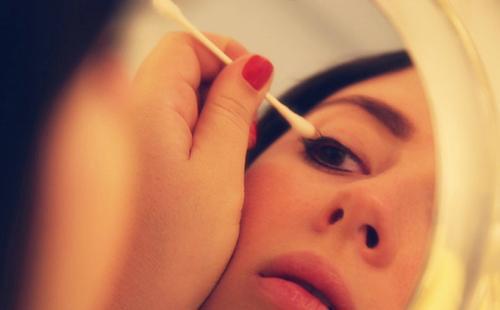 Девушка смотрит в зеркало и наносит масло на веки