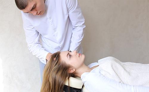 Мужчина делает массаж головы женщине