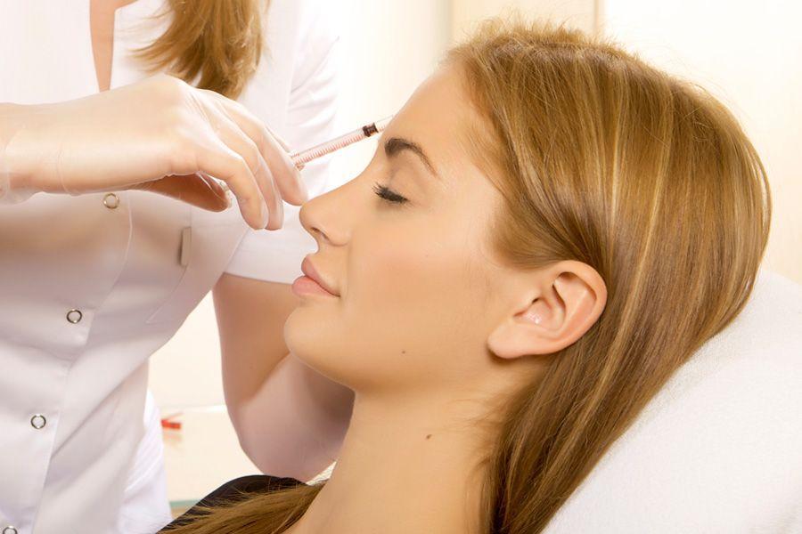 Девушке делают мезотерапию лица в салоне красоты