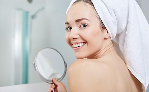 Женщина держит зеркало и улыбается