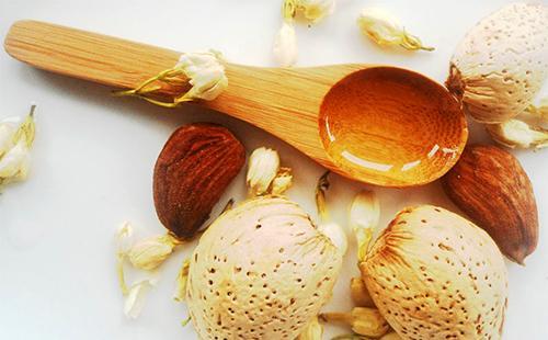 Цветы, орехи и золотое масло в деревянной ложке