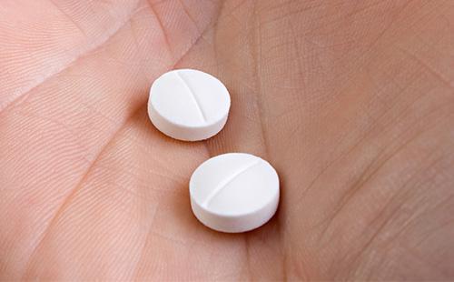 Белые таблетки в руках