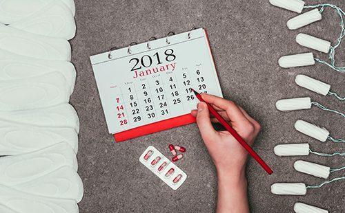 Женщина обложилась средствами гигиены и пишет в календаре