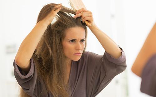 Женщина рассматривает свои волосы