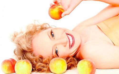 Девушка держит персик в руке