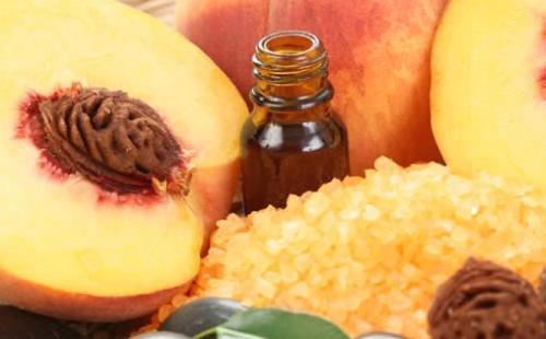Разрезанный персик и масло в пузырьке