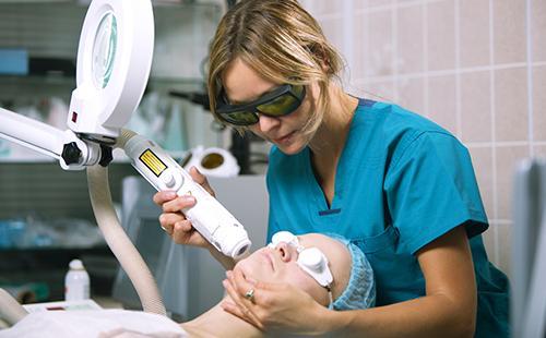 Косметолог обрабатывает лицо пациентки лазером