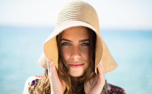 Девушка у моря в большой шляпе