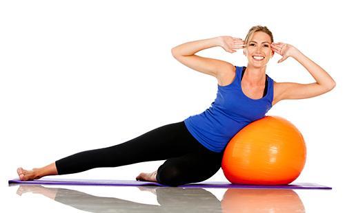 Женщина делает упражнения на фитболе