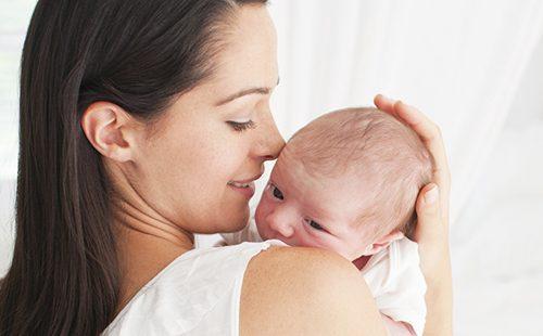 Мама с улыбкой держит новорожденного