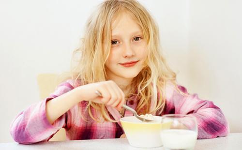Девочка с ангельским лицом с удовольствием ест кашу