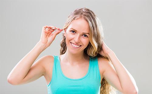Девушка чистит ухо