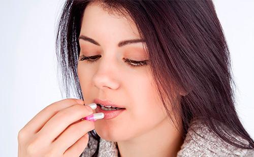 Девушка принимает капсулу с лекарством