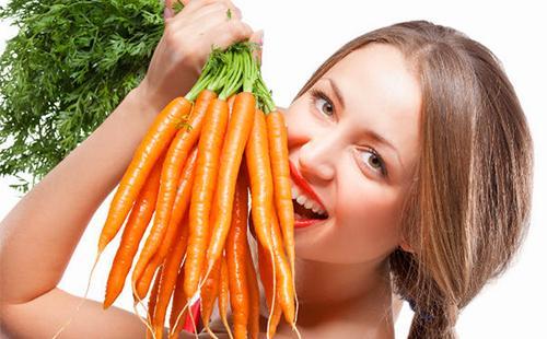 Весёлая девушка держит целый пучок моркови