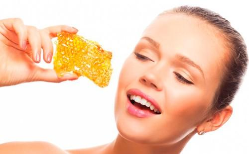 Девушка держит в руках соты с медом