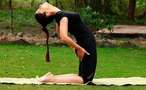 Женщина на коврике занимается пилатесом