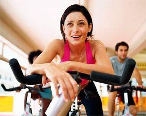 Девушка крутит педали в фитнес-центре