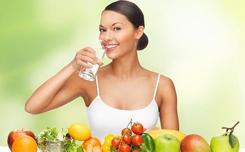 Женщина в белом топе со стаканом воды и фруктами